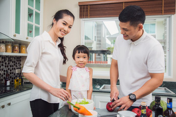 father, mother and daughter cooking for dinner togather, this picture can use for family, food, kitchen and house concept