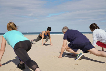 Senior people exercising on the beach with sports coach