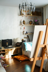 Artistic equipment: artist paper or canvas on easel in an artist studio. Cozy room of creative people. Vertical photo