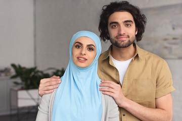muslim boyfriend hugging girlfriend in hijab at home