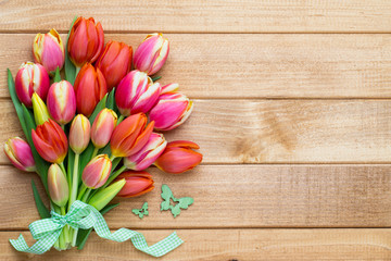 Spring easter tulips in bucket on wooden vintage background.