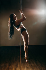 Beautiful slim girl with pylon. Female pole dancer woman dancing on a pole on a darck background. Strong and graceful girl dancing on pylon. Girl easily performs complex dance steps on pylon