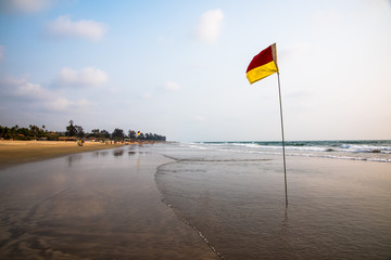 Red and yellow safety flag on long sandy beach
