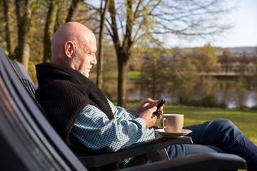 Senior man holding smart phone relaxing on sunny day