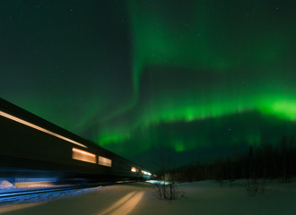 Walking train and aurora borealis over the tundra