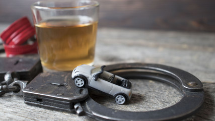 Metal handcuffs, car, whiskey glass. Drink and driving concept.