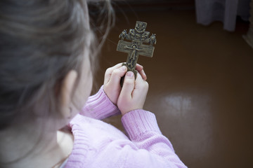 girl with a cross in her hands closeup
