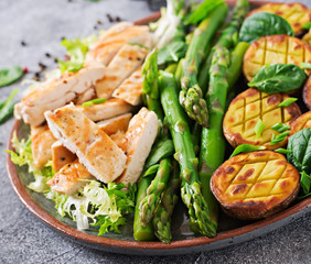 Chicken fillet cooked on a grill with a garnish of asparagus and baked potatoes. Dietary menu. Healthy food.