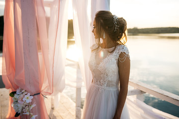 Beautiful bride standing at sunset