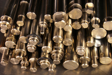 Shiny metal round bars and rods on steel background