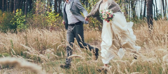 a marrige couple are running happing in the forest on the glade of spikelets