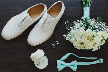Leather white groom wedding shoes on the wooden background in sun rays. Rings, bow tie and cufflinks with elegant bouquet. Elegant wedding details flat lay. Tiffany light blue color.