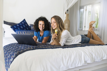 Two smiling women lying in bed shopping online with credit card and laptop