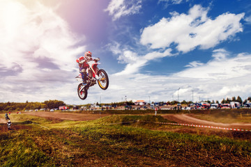 Racer on dirtbike motorcycle jumps and takes off over the track, in background opponent is catching up. Concept primacy, rivalry, competition, extreme