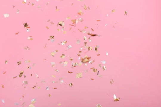 Golden confetti on pink background