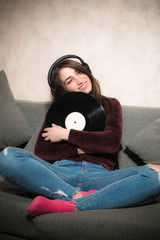 Young woman listening music with vinyl record
