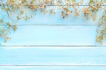 Flowers composition.  Frame made of white wild flowers on blue wooden background.  Concept flowers of spring, top view and border design,