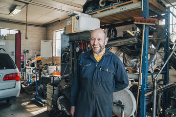 Portrait of smiling male mechanic standing sat car repair shop