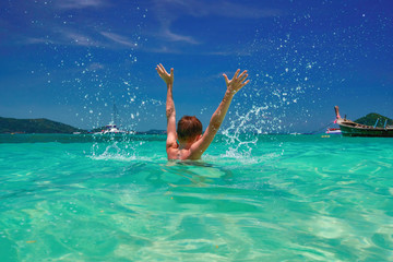 Child splashing in water. Cheerful boy (12 years old) hands up in turquoise tropical sea. Seascape, bright sky and sea. Back view.