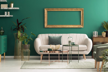 Beige sofa in green interior