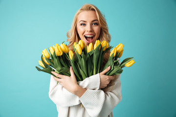 Portrait of a joyful young blonde woman in sweater