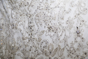 Delicate lace fabric of white wedding dress