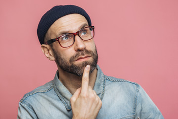 Close up shot of pleasant looking bearded male with thoughtful expression, keeps finger on chin, looks thoughtfully up, wears glasses and fashionable hat, poses against pink studio background