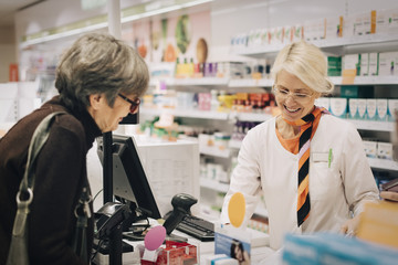 Smiling female owner standing with senior customer at checkout in pharmacy store