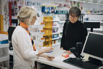 Female owner holding prescription paper with senior customer standing at checkout in pharmacy store