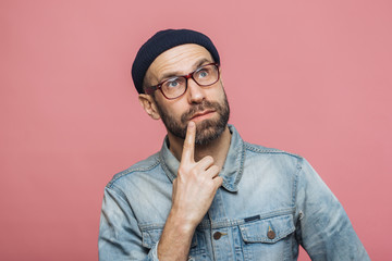 Thoughtful bearded male being deep in thoughts, looks with pensive expression into camera, concentrated on something, poses against pink background. People, facial expressions, daydreaming concept