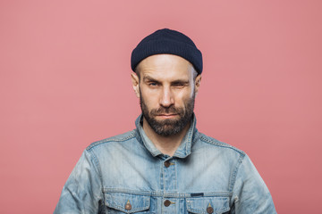 Photo of good looking bearded male blinks eye and looks seriously into camera, wears denim jacket and black hat, isolated over pink background. Stylish man with stubble poses in studio alone.