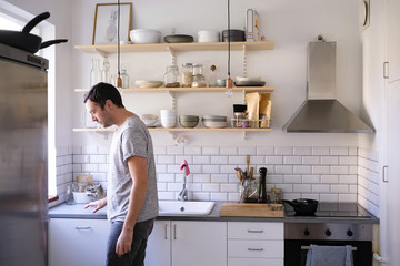 Side view of man standing by kitchen counter at home