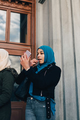 Low angle view of young Muslim woman applying lipstick looking into mobile phone by friend against building