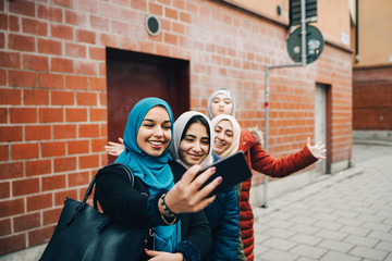 Happy woman taking selfie with female friends on sidewalk against building in city