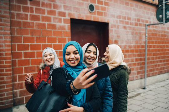 Happy young Muslim woman taking selfie with female friends on sidewalk against building in city