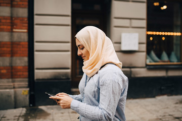 Side view of young woman using smart phone while walking on street in city