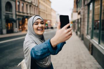 Cheerful young Muslim woman wearing hijab taking selfie on sidewalk in city