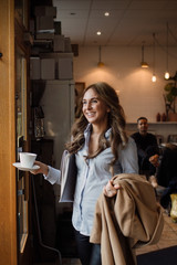 Happy young woman walking with coffee cup and overcoat at cafe