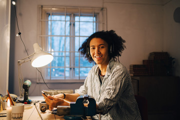 Portrait of smiling technician working on equipment while listening music at desk in workshop
