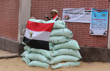 An Egyptian army soldier stands guard outside a polling station during the last day of the presidential election in Cairo