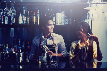 couple bartender shaking cocktails in counter at nightclub.