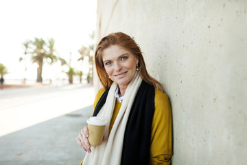 Portrait of confident mature woman with disposable cup standing against wall in city