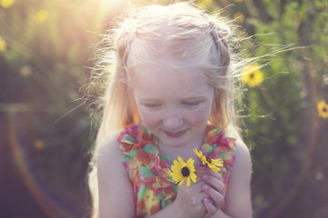 Cute girl with yellow flowers on field during sunny day