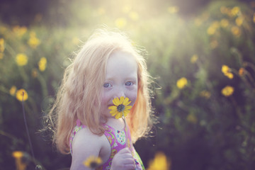 Portrait of cute girl with yellow flower on field during sunny day