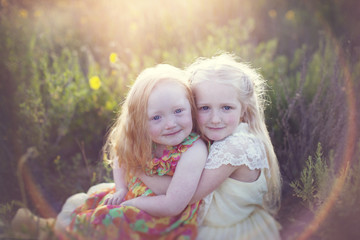 Portrait of cute sisters sitting on field during sunny day
