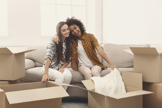 Two young women unpacking moving boxes