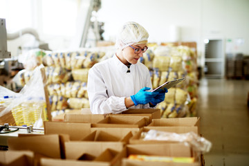 Young beautiful worried female worker in sterile clothes is using a tablet while being leaned against the stacks of open boxes inside of factory storage.