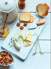 Cheese plate served with crackers, honey and nuts. Camembert on white wood serving board over white texture background. Appetizer theme. Top view with space