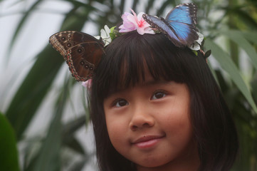 Ruhi Samir, aged 8, poses for a photograph with a butterfly during an event to launch the Sensational Butterflies exhibition at the Natural History Museum in London