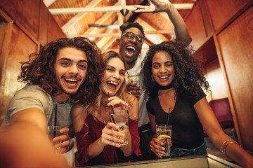 Group of friends taking selfie at night club party
